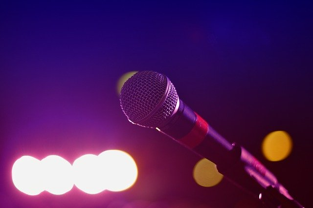 microphone against a dark purple and pink back drop with bright lights