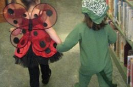 photo of toddlers in costume walking in library Halloween parade