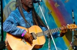 photo of Asheba playing guitar with rainbow backdrop; used by permission of Asheba