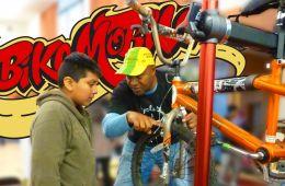 BikeMobile staff with a child repairing a bike.