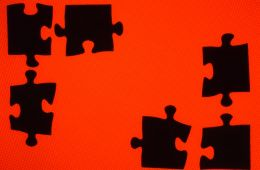 Black puzzle pieces in red background