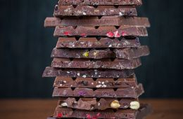 Side view of a tall stack of various kinds of chocolate bars