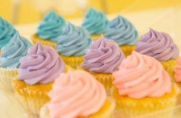 Yellow cupcakes with pastel colored frosting.