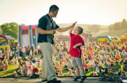 photo of magician Dan Chan with young audience member