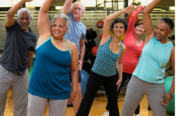 six adults stretching, dancing and smiling