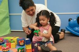 photo of child and woman playing with blocks