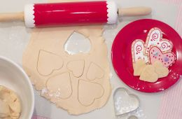 cookie dough rolled out with heart-shapes cut from it, shown with a bowl of dough, rolling pin and iced heart-shaped cookies.