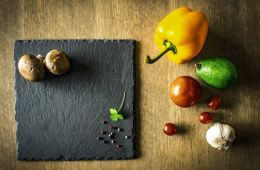 mushrooms, peppercorns, and herbs on slate and peppers, avocado, tomatoes, and garlic on wood counter surface.