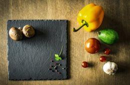 Slate cutting board with mushrooms, onions, garlic, black pepper.