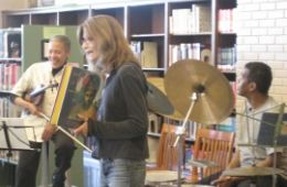 photo of India Cooke with violin, Lisa DiPrima presenting story, and Don Robinson at drums