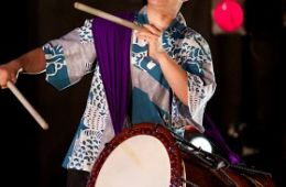 photo of Kristy Oshiro playing taiko drum attached by a sling; permission of Kristy Oshiro