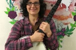 photo of Maggie Lind holding banjo in front of mural; photo used by permission of the artist