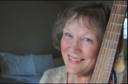 close up photograph of MaryLee Sunseri leaning on guitar