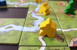 Three yellow playing pieces on a board game
