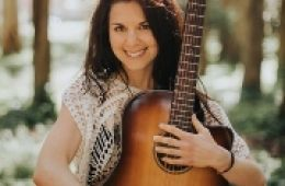 photo of musician Megan Schoenbohm hugging her guitar