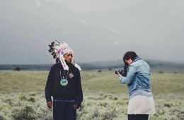 Photographer Matika Wilbur taking a picture of a Native American man wearing a traditional head covering.