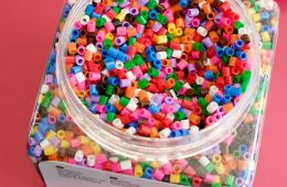 Large plastic jar filled with perler beads