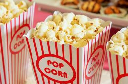 popcorn in red and white striped paper containers.