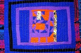 photo of a freeform quilt with blue, red, and purple pieces