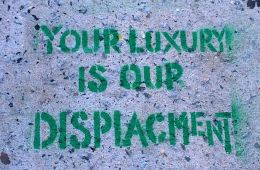 """""""Your luxury is our displacement"""" spray painted in green on concrete"""