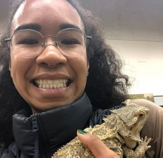 close up photo of geologist Pinkie Young holding a bearded dragon reptile while smiling into the camera