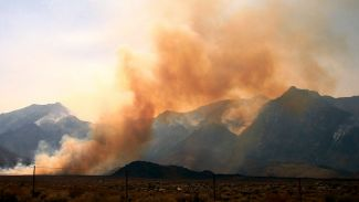 photo of orange smoke in front of gray mountains with a wire fence in front