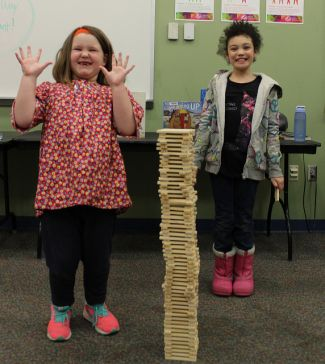 kids showing off their KEVA plank tower