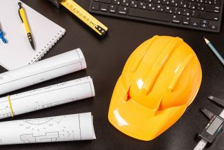 photo of yellow hard hat on a black desk with blueprints and computer keyboard