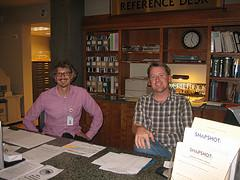 Two librarians sitting at the Reference Desk ready to help