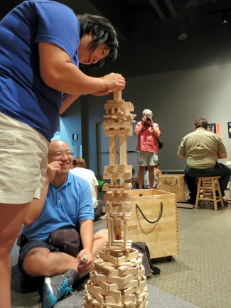 "photo of adults building with KEVA planks; ""Just One More Plank"" by Ruth Hartnap is licensed under CC BY 2.0"