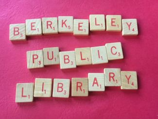 Scrabble tiles spelling out Berkeley Public Library on pink background.