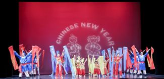 """photo of dancers in front of screen that says """"Chinese New Year"""""""