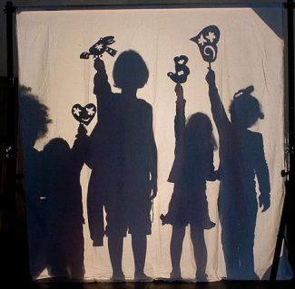 Behind the screen. Children playing with shadow puppets