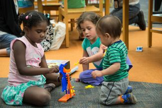 photo of three kids of various ages playing with a learning game; photo credit Terry Lorant Photography