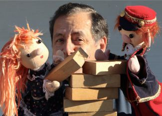 photo of Joe Leon, puppeteer, with two of his puppets from the show Beto the Builder