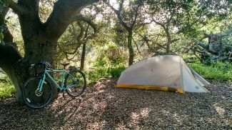 A tent in the woods with a bike nearby.  Photo by Rachel Jacobson