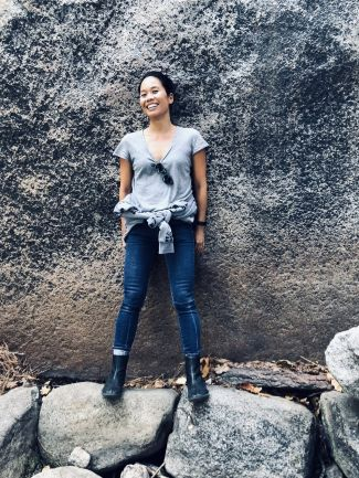 photo of author Bonnie Tsui standing against a big rock while balancing on two smaller rocks