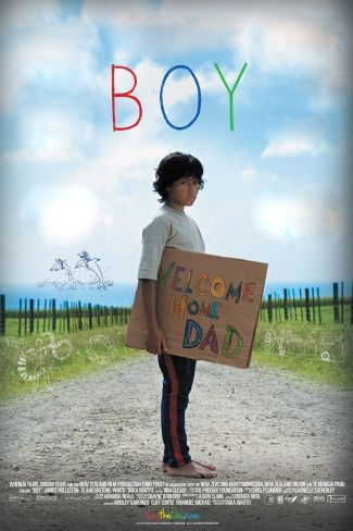"movie poster of ""Boy"" showing actor James Rolleston holding a handmade sign that reads ""Welcome home, Dad""."