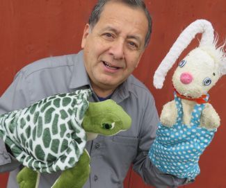 photo of Joe Leon of Caterpillar Puppets holding rabbit and turtle puppets