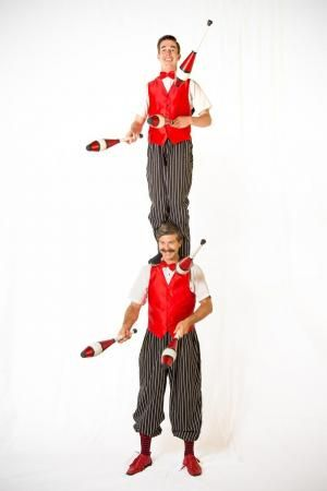 Mr. Quick and Mr. Moustache from Circus of Smiles; Mr. Quick is standing on Mr. Moustache's shoulders; they are juggling