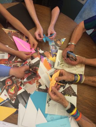 photo of hands holding origami cranes while folding cranes at Peace Day event