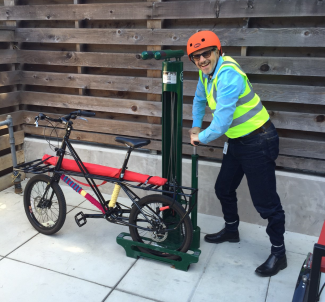 Ilan pumping the tire on the Library on Wheels companion bike.