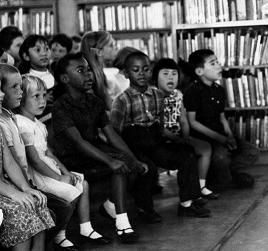 Children sitting in rows in front of a wall of bookcases