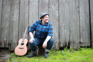 Singer, Dill, pictured outside sitting on a stump with guitar next to them.