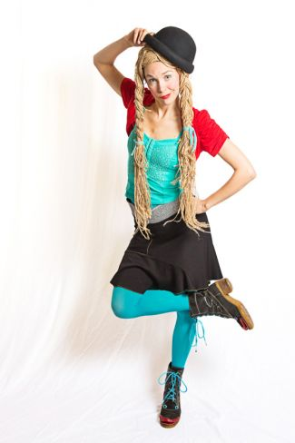 photo of Drea Lusion posing with knee crossed over leg and hand on hat
