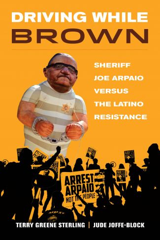Features a balloon that looks like Joe Arpaio in a prisoner's outfit with with chains around his wrists on orange background.