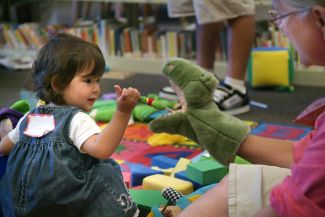 photo of child looking at puppet