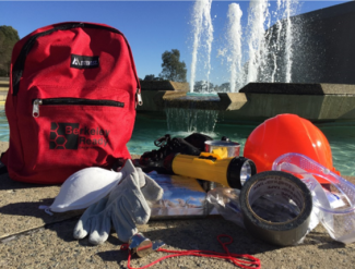 contents of a red emergency backpack displayed before a fountain on a sunny day