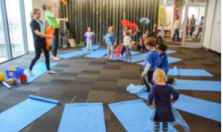 yoga mats in a circle with adults and kids standing, ready to stretch