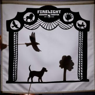 photo of a shadow puppet show with a bird, dog and a tree